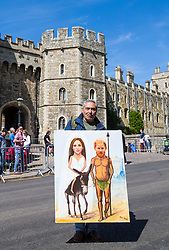 Satirical political artist Kaya Mar poses outside Windsor Castle with a royal wedding painting he created as excitement builds up in Windsor ahead of the royal wedding on Saturday 19th May when HRH Prince Harry weds actress Megan Markle. Windsor, May 17 2018.