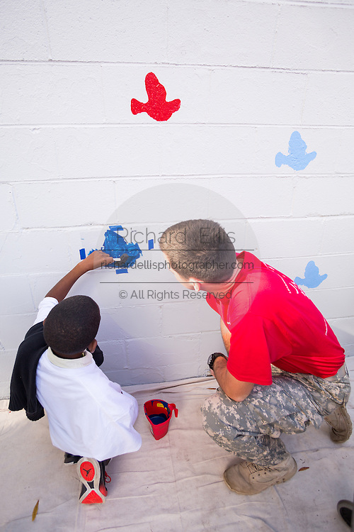 A young boy is helped by a Citadel Military college cadet to paint a dove on the Charleston Strong wall mural October 21, 2015 in Charleston, South Carolina. The wall is to commemorate the mass shooting at the historic Mother Emanuel African Methodist Episcopal Church last June.