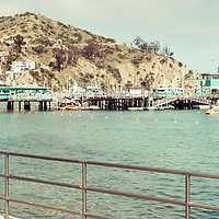 Catalina Island tiki umbrella retro panorama photo with the Catalina Casino, Avalon Pier, and Avalon Harbor. Santa Catalina Island is a popular travel destination off the coast of Southern California in the United States of America.  Copyright ⓒ 2017 Paul Velgos with All Rights Reserved.