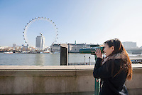 Young woman looking at London Eye through stationary viewer at London; England; UK