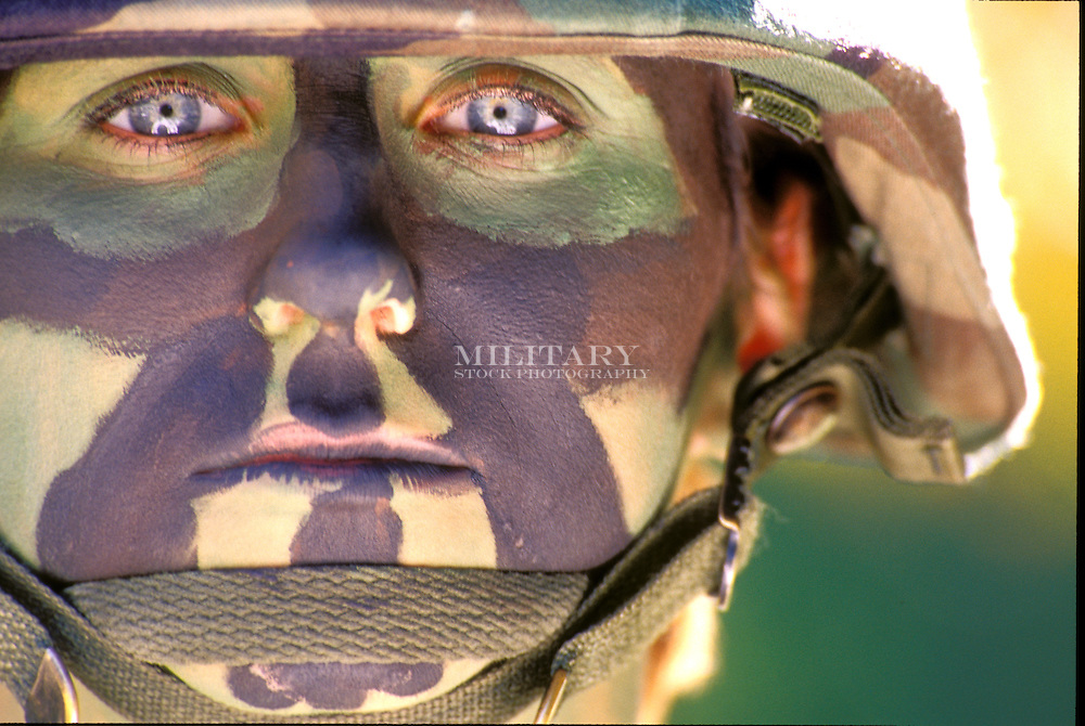 Model-released female in woodland pattern BDU and US Army pattern camouflage face paint.