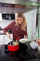 Woman serving pasta in bowl at kitchen counter
