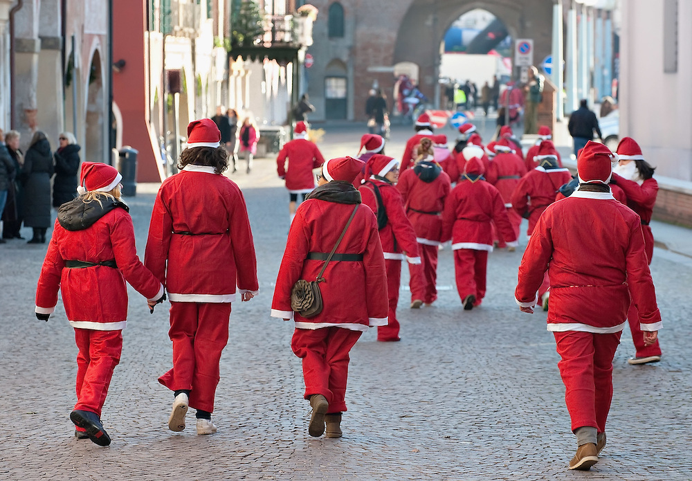 NOALE, ITALY - DECEMBER 18:  Participants dressed as Father Christmas walk toward the start of the Noale Santa Run on December 18, 2011 in Noale, Italy. Close to two thousand people participated in the third annual Noale Santa Run, one of the largest non competitive Santa Run in Italy.