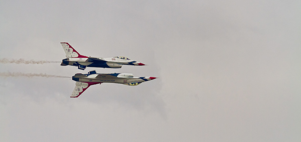 Two Thunderbird jets flying in formation, one of them inverted.