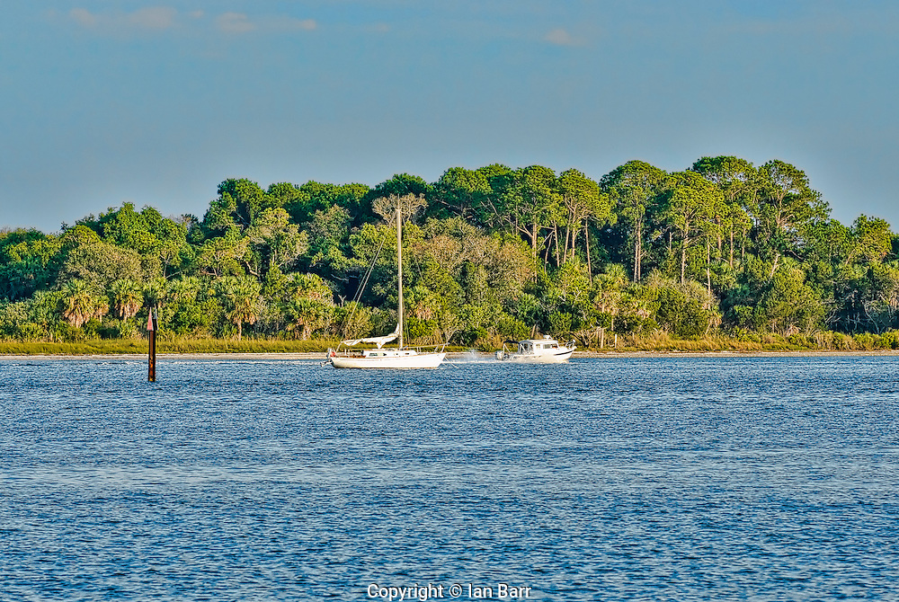 Motorboat passes anchored sailboat off of Cedar Key,Florida.