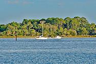 Motorboat passes anchored sailboat off of Cedar Key,Florida.