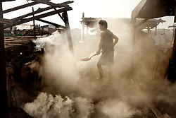 Nilo making coal in a slum area in Manila, many of the coal makers have serious problems with breathing and TB . Manila, Philippines