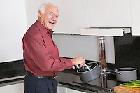 Portrait of cheerful elderly man preparing food in kitchen