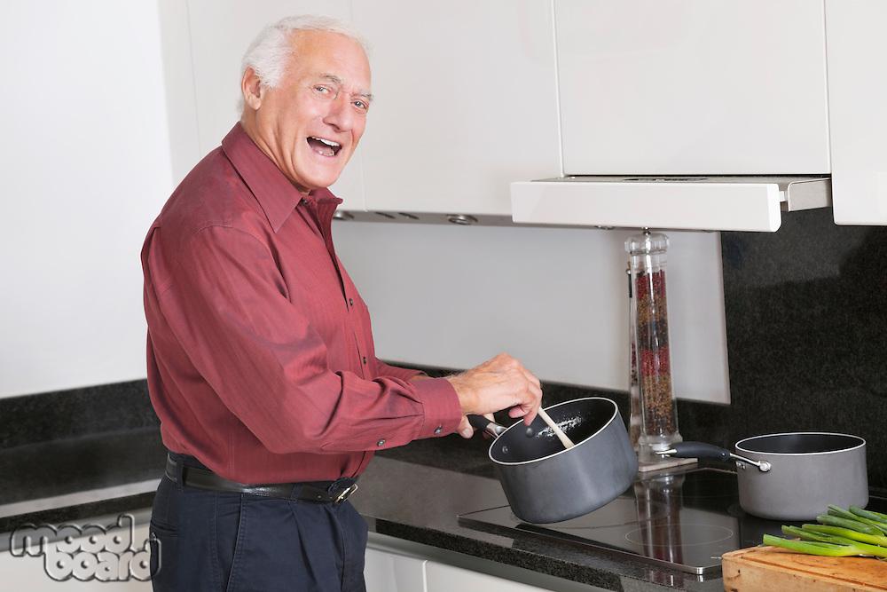 Portrait of cheerful elderly man preparing food in kitchen