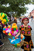 Young women dressed in traditional costumes parade in a comparsas past the Santo Domingo de Guzmán Church during the Day of the Dead Festival known in Spanish as Día de Muertos in Oaxaca, Mexico.