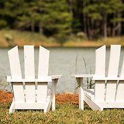 A pair of white Adirondeck chairs on the waterline of the Chesapeake Bay on Maryland's Eastern Shore.