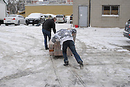 A young man pushes a sofa with the help of an older man across a snowy parking lot at Worth a Second Look, a second hand store in Kitchener, Ontario, Canada. Both men participate in Job Cafe, a casual work program of The Working Centre.