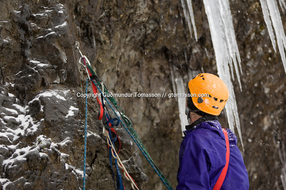 "Róbert Halldórsson preparing for the first ascent of the ice climb "" Krókodílamaðurinn"" M6, 30m, at Breiðdalur. East Iceland."