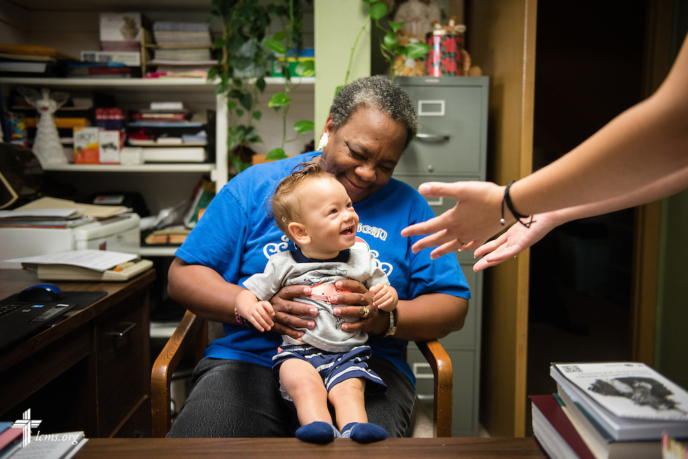 House manager Ronne Murray holds Ezekiel Vela for the waiting arms of his mother Tiffany Busse during a lighthearted moment at A Place of Refuge on Wednesday, Sept. 2, 2015, in Milwaukee, Wis. LCMS Communications/Erik M. Lunsford