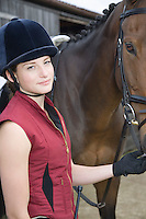 Portrait of girl holding horse outdoors
