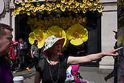 Woman in floral sun hat in front of Apple Watch window display in Selfridges, central London.