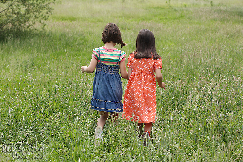 Two girls (7-9) holding hands in field