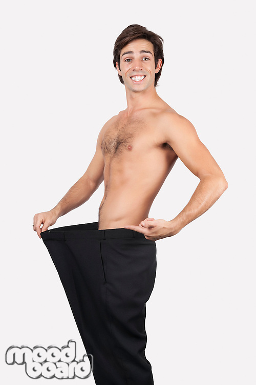 Portrait of happy young man wearing oversized pants against gray background
