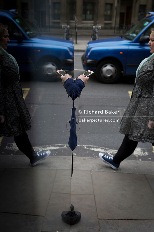 A symmetrical reflection of a lady using her phone at a bus stop in The Strand, on 4th May 2017, in London, England.