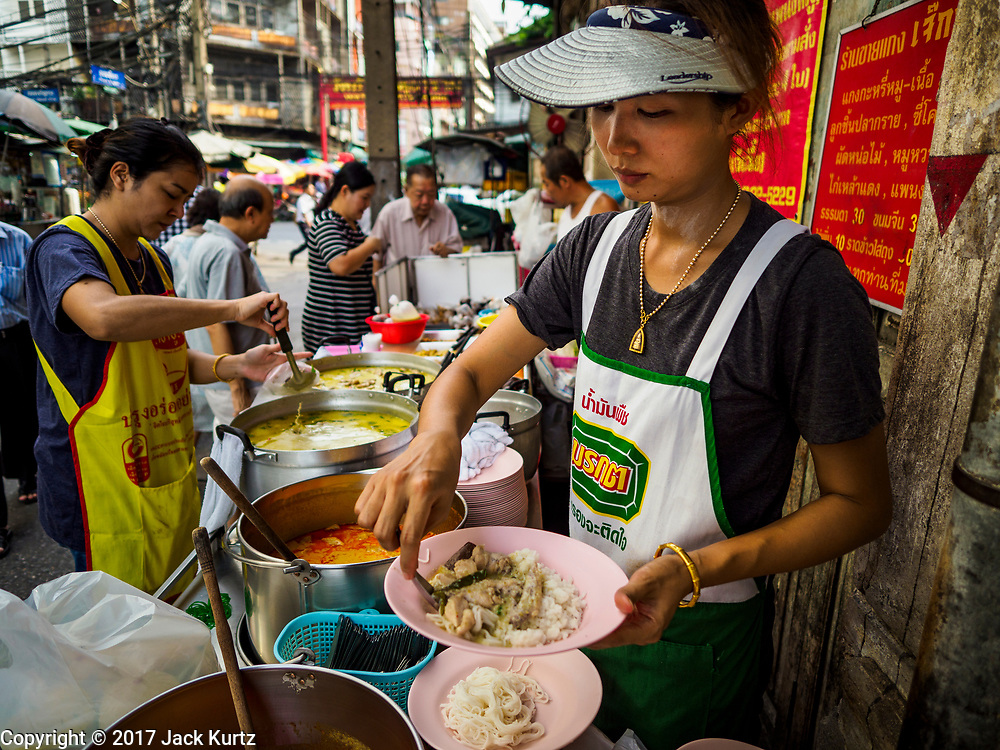 """18 MAY 2017 - BANGKOK, THAILAND: A woman serves curry at Jek Pui curry stand, a popular street food stall for curry dishes. City officials in Bangkok have taken steps to rein in street food vendors. The steps were originally reported as a """"ban"""" on street food, but after an uproar in local and international news outlets, city officials said street food vendors wouldn't be banned but would be regulated, undergo health inspections and be restricted to certain hours on major streets. On Yaowarat Road, in the heart of Bangkok's touristy Chinatown, the city has closed some traffic lanes to facilitate the vendors. But in other parts of the city, the vendors have been moved off of major streets and sidewalks.      PHOTO BY JACK KURTZ"""