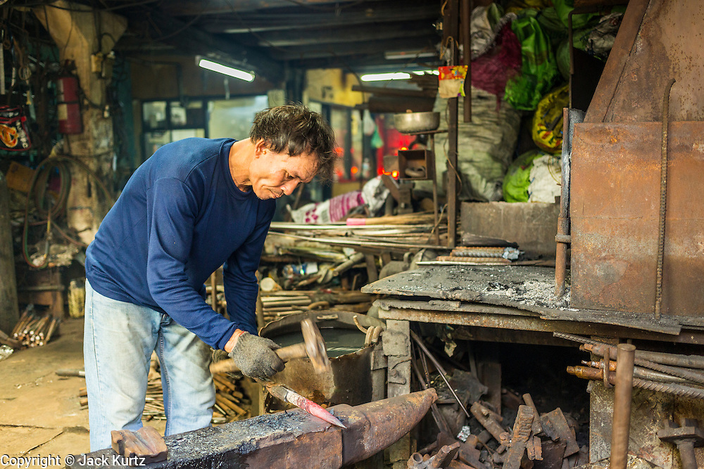 26 APRIL 2013 - BANGKOK, THAILAND:    A man uses traditional blacksmithing methods to make metal stakes in a workshop in Talat Noi. The Talat Noi neighborhood in Bangkok started as a blacksmith's quarter. As cars and buses replaced horse and buggy, the blacksmiths became mechanics and now the area is lined with car mechanics' shops. It is one the last neighborhoods in Bangkok that still has some original shophouses and pre World War II architecture. It is also home to a  Teo Chew Chinese emigrant community.      PHOTO BY JACK KURTZ