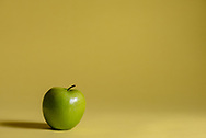 One green apple on a yellow background.