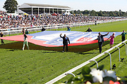 York Racecourse employees from all departments parade a large flag prior to the running of The Sky Bet Ebor Handicap over 1m 6f (£1,000,000)  during the Ebor Festival at York Racecourse, York, United Kingdom on 24 August 2019.