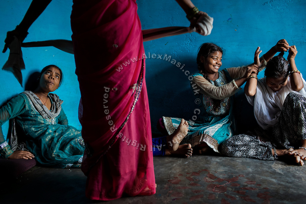 Poonam, 13, (centre) is pulling the hair of her older sister Arti, 19, (right) while their sister Jyoti, 14, (left) is talking to their mother, as she dries her hair in their newly built home in Oriya Basti, one of the water-contaminated colonies in Bhopal, central India, near the abandoned Union Carbide (now DOW Chemical) industrial complex, site of the infamous '1984 Gas Disaster'.