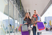 Happy female friends with shopping bags walking on sidewalk
