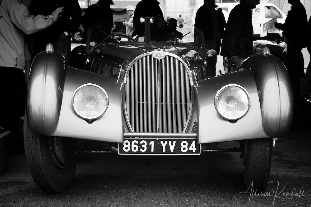 Car fans mingle with classic automobiles in the paddock of a vintage racing event.