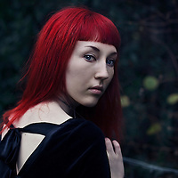 Portrait of a young female with red hair, blue eyes and pale skin, wearing a black velvet top looking at the camera, over her shoulder, with green foliage background.