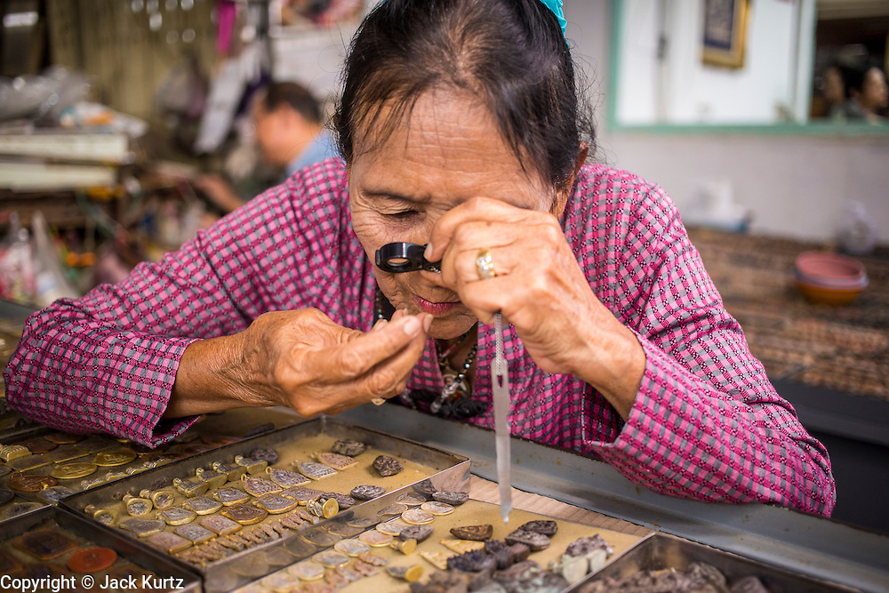 05 OCTOBER 2012 - BANGKOK, THAILAND:  A woman uses a magnifying glass while she shops for amulets in the amulet market in Bangkok. Hundreds of vendors sell amulet and Buddhist religious paraphernalia to people in the area north of the Grand Palace near Wat Maharat in Bangkok.        PHOTO BY JACK KURTZ