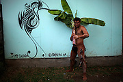 A maori teenager displays his body tattooed in volcanic mud and holds a banano plant as he poses for a photo aside a stylized graffiti depicting a bird, symbol of the Rapa Nui culture during a festival named Tapati Rapa Nui in Hanga Roa, Rapa Nui, Saturday, Feb. 12, 2011. Boundaries of race become blurrier in the most important Polynesian island, as Chile the country that conquered the territory in the XIX century, tries to push globalization into the island with the same power the Pacific waves reach its rocky shores.