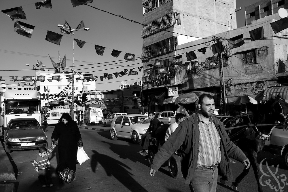 Gaza Palestinians walk under flags of the militant group HAMAS across a busy street in Gaza City, Gaza December 19, 2009. The group, which seized complete control of the strip in 2007 has seemingly endured despite an international border blockade lead by Israel and Egypt, and appears to have retained popular support of the majority of Gaza Palestinians.