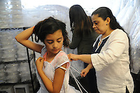 Ana Suarez, right, helps Jalyssa Garibay, 9, at her fitting for a First Communion dress at Alicia's Boutique in Salinas.
