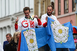 © Licensed to London News Pictures. 28/09/2016. Leeds, UK. Alistair Brownlee and Gordon Benson atop an open top bus at the Olympic and Paralympic parade in Leeds. Yorkshire's Olympic and Paralympic stars receive a heroes' welcome during an open top bus parade in Leeds, West Yorkshire. . Photo credit : Ian Hinchliffe/LNP