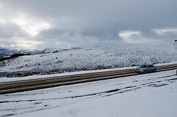 © Licensed to London News Pictures. 27/12/2014. Horseshoe Pass, Denbighshire, UK. A car travels up the pass road. Snow continues to fall on high ground in Wales. Photo credit: Graham M. Lawrence/LNP
