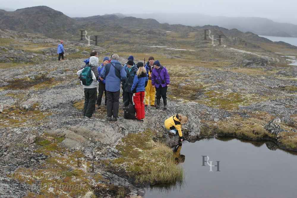 Passengers from small expedtion cruise ship sitting in distance, Clipper Adventurer, hike across vast rocky landscape of Eqalugssuit, Greenland