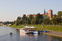 small boat passes river craft moored on the river vistula with the wawel castle behind, krakow poland. soft afternoon sunlight and clear sky sets the scene