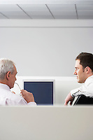 Two businessmen sitting in office cubicle back view