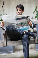 Happy Indian businessman reading newspaper while sitting on bench