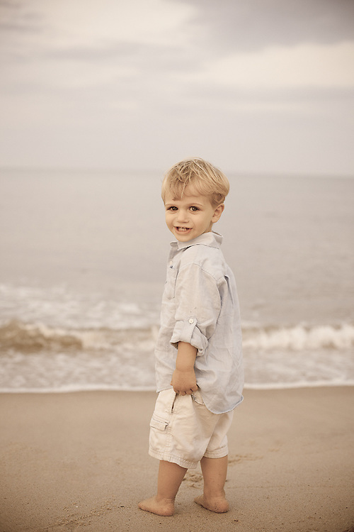Aged portrait of a little boy looking over his shoulder at Nauset Beach in Orleans on Cape Cod