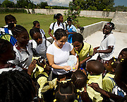 "Priscilla Zelaya holds out a wand for school children to blow bubbles. Spontaneously, a group of 12 Floridians decided to travel to Haiti for a week to help in any way they could. For two months they prepared to instruct students at three Port-au-Prince schools in Biblical and moral principals, pray for the children and distribute gifts. ""My heart is full of love and compassion for the beautiful people of Haiti,"" Zelaya said."