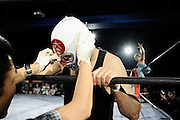 A wrestler gets some medical attention for his bloodied face while his opponent gestures while sitting on the ropes  in a bout  at Doglegs, an event for wrestlers with physical and mental handicaps in Tokyo, Japan.