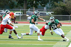 19 September 2015:   Andrew Javorka attempts to get between runner Maurice Shoemaker-Gilmore as Adrean Johnson lunges for his feet during an NCAA division 3 football game between the Simpson College Storm and the Illinois Wesleyan Titans in Tucci Stadium on Wilder Field, Bloomington IL