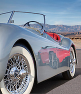 Close up silver 1954 XK 120 Jaguar with reflection of a red 2014  Jaguar F-Type. Photographed in the Desert of Palm Springs, CA