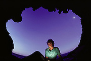 Peter Menzel, self-portrait, at dawn in sleeping bag in seaside cave at Dinosaur Cove, Cape Otway, southern Australia. Dinosaur cove is the world's first mine developed specifically for paleontology - normally the scientists rely on commercial mining to make the excavations. The site is of particular interest as the fossils found date from about 100 million years ago, when Australia was much closer to the South Pole than today. MODEL RELEASED [1989]