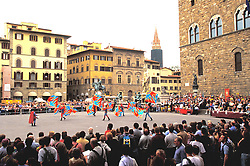 Florence, Italy: Costumed performers representing various regions of Italy compete in flag competitions in the main square of the city.  Palazzo Vecchio is on the right.
