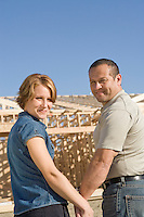 Mid-adult couple at construction site, portrait