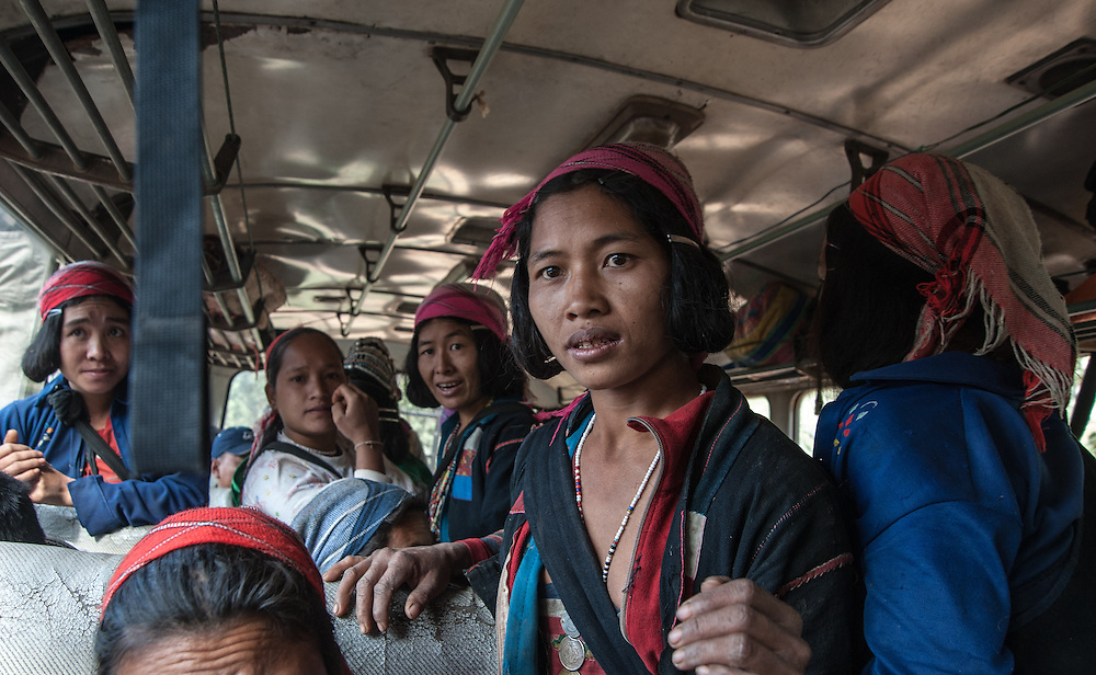 Tribal woman look on with curiosity towards foreigners riding on bus in a remote part of northern Laos
